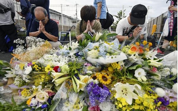 Người dân đặt hoa cầu nguyện cho nạn nhân vụ hỏa hoạn.
