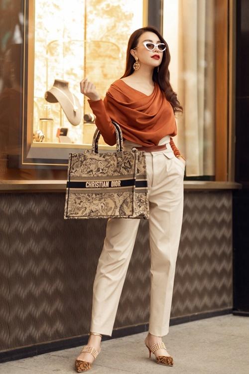 Thi thoảng, Trà Ngọc Hằng chọn style kín đáo để dạo phố. Mẫu áo xếp nếp mix cùng quần cạp cao, túi Christian Dior tôn lên vẻ sang trọng cho người đẹp Cà Mau.
