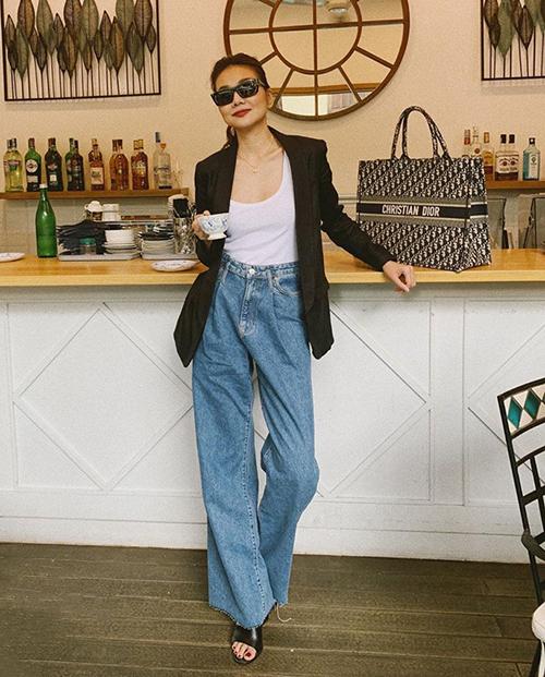 Thanh Hằng mặc quần jeans ống rộng và blazer đậm chất menswear, kết hợp cùng túi Christian Dior size lớn.