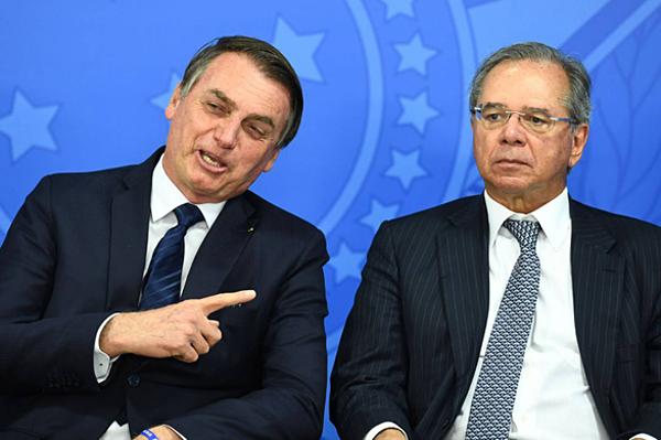 Tổng thống Brazil Jair Bolsonaro (trái) trong một ảnh chụp chung với Bộ trưởng kinh tế Brazil Paulo Guedes hồi tháng 7. Ảnh: AFP.