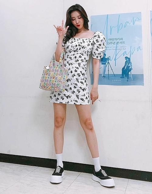 Sunmi nữ tính khi diện váy hoa nhí và túi hoa nhưng vẫn năng động với đôi sneaker đen đế trắng.