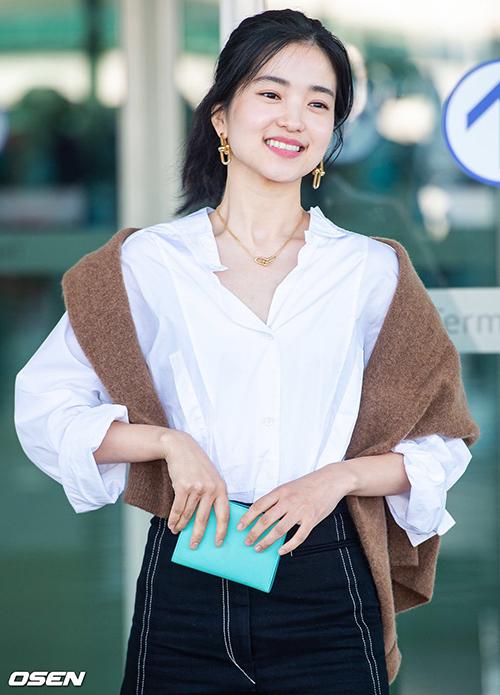 Diễn viên  Kim Tae Ri với phong cách thời trang thanh lịch, tươi sáng cũng dùng áo len khoác hờ trên vai để thêm phần phóng khoáng cho set đồ sân bay