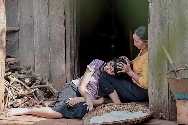 HHen Niê tựa đầu vào mẹ bên ngoài ngôi nhà gỗ truyền thống của người Ê-đê. Trước đó, cô dùng số tiền kiếm được, tu sửa ngôi nhà cũ thêm vững chãi.