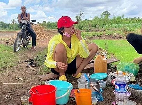 HHen Niê ngồi ăn cơm với cá khô sau khi ra ruộng cấy. Mỗi lần trở về nhà, cô thường đi dép tổ ong, đội nón lưỡi trai.