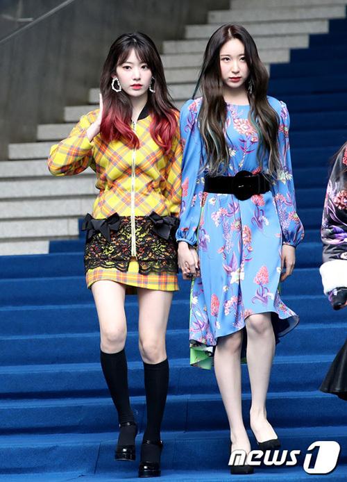 Sakura và Chae Yeon (phải) nắm tay nhau đi trên thảm xanh. Sau khi hoạt động ở Hàn, Sakura được nâng tầm nhan sắc, phong cách thời trang cũng trở nên ấn tượng hơn trước.