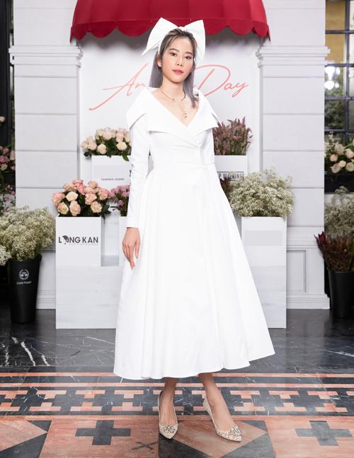 Nam Em mặc váy trắng thanh lịch, kết hợp phụ kiện nơ siêu to khổng lồ.