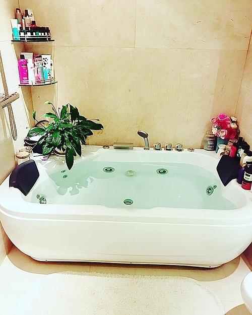 Phòng tắm diện tích nhỏ được Phạm Hương trang trí bằng hoa giả, cây xanh.